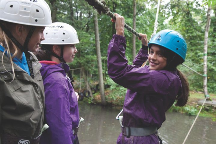 School girls in a wood about to go on a zip line with helmets and harnesses on