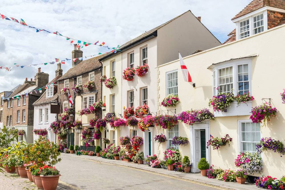 Seafront houses with flowers, flags and banners in the town of Deal