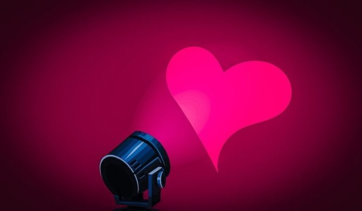 a pink heart on a wall with a light shining at it